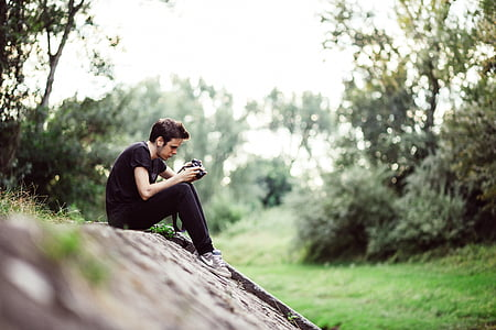 man browsing camera while sitting on the cliff