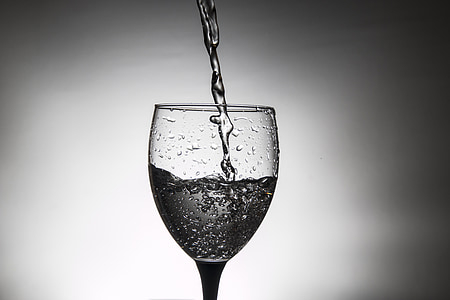 pouring water on wine glass grayscale photography