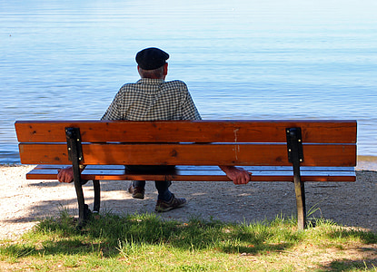 person sitting on brown wooden bench