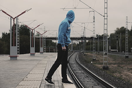 man wearing blue pullover hoodie walking on railroad photography during daytime