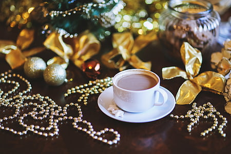 cup of coffee on white ceramic saucer beside silver-colored beads, gold ribbons, and silver baubles Christmas ornaments