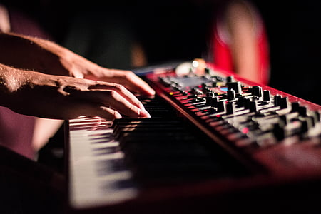 person playing red electronic keyboard