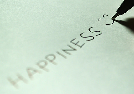 person writes happiness with smiley