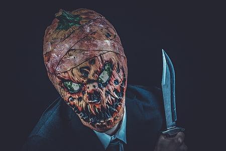 pumpkin head person holding knife