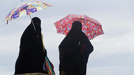 two person standing holding umbrellas