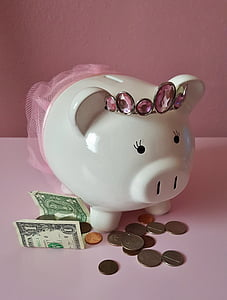 white ceramic piggy bank near coins and banknote