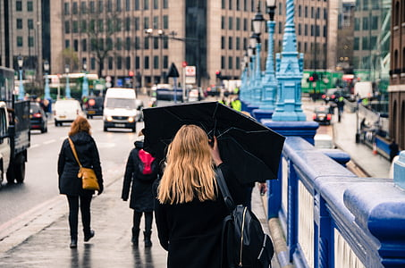 woman holding umbrella while walking on roadside during daytime