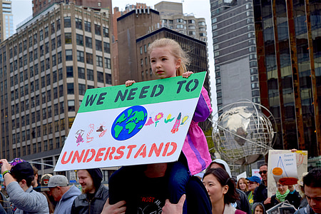 girl sitting on man's shoulder while holding We need to understand signage