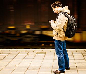 man standing white using smartphone