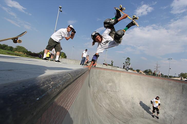 man skateboarding under blue sky