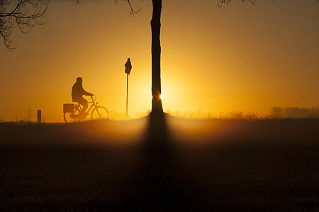 silhouette of person riding bicycle
