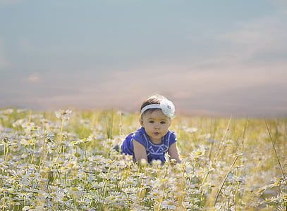baby about to crawl and surrounded by flowers