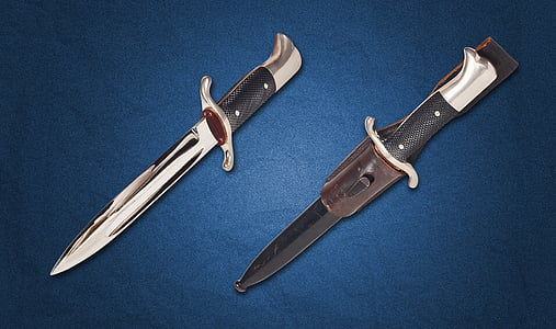 two silver and black dagger with sheath on top of blue surface