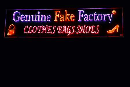 Genuine Fake Factory neon signage turned on