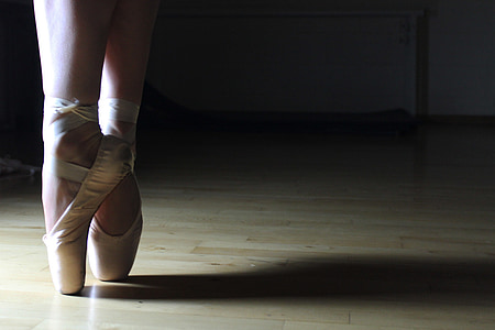 person wearing white ballet shoes doing ballet dance