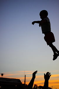 silhouette photography of child on air with a person catching him