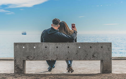 man and woman sitting on bench beside sea