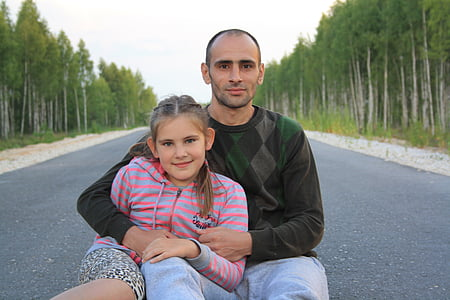 man and girl sitting in the middle of the road