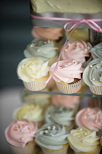 selective focus photography of cupcakes on glass shelf