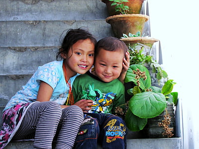 smiling girl and boy sitting on staircase beside plants during daytime