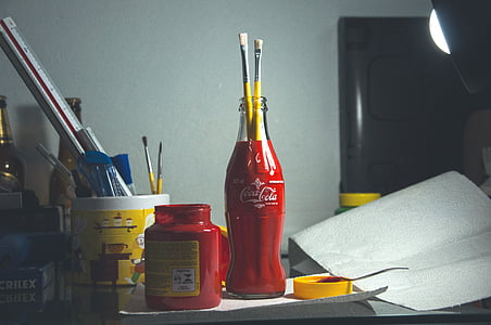 red Coca-Cola glass bottle with two paintbrushes