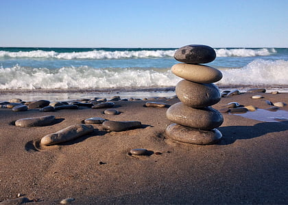 photo of five stacked stones on the beach