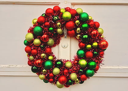 red, green, and gold bauble wreath hanged on white wall
