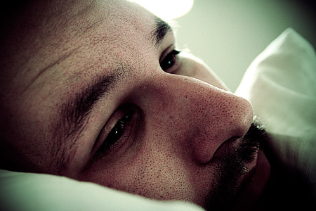 micro photograph of man lying on pillow