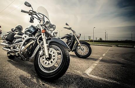 photo of black chopper motorcycle beside motorcycle