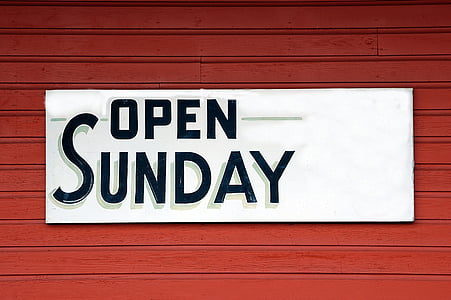 Open Sunday signage on red steel bar