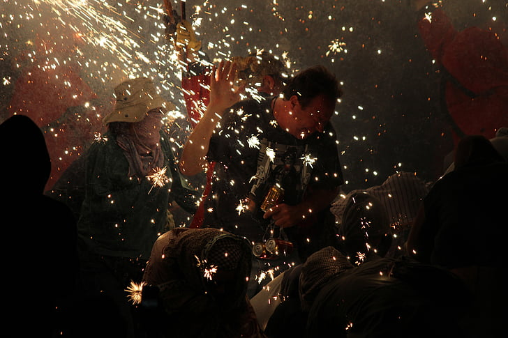 man standing surrounded with people lighting sparklers