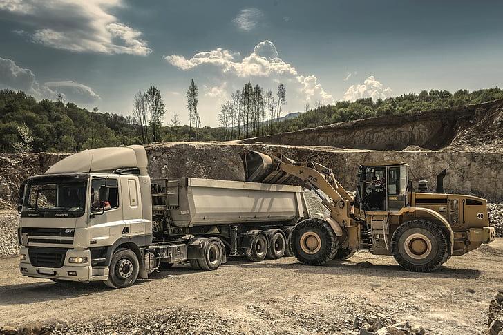 white and gray truck and yellow heavy equipment