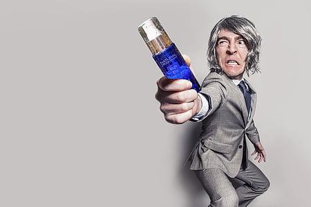 man in gray label suit jacket holding blue fragrance bottle