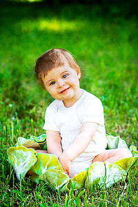 smiling baby sitting on green grass