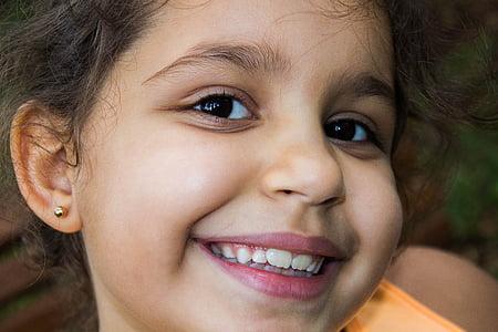 smiling girl wearing orange top
