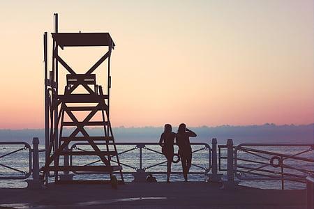 two women beside lifeguard chair
