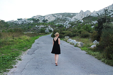 woman wearing black sleeveless dress on gray concrete road