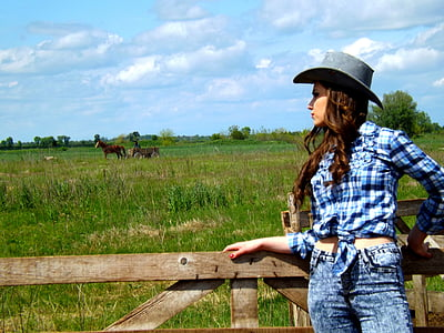 woman standing near brown wooden rail looking at brown horse