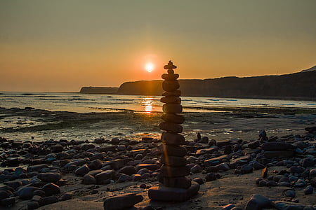 cairn on seashore during daytime