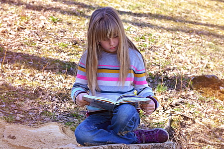 girl reading book sitting on green grass at daytime