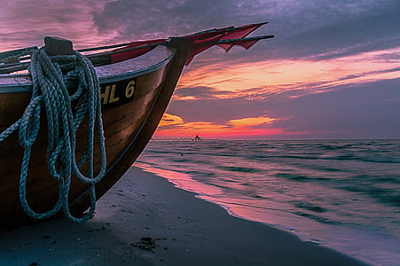 boat on seashore under black clouds