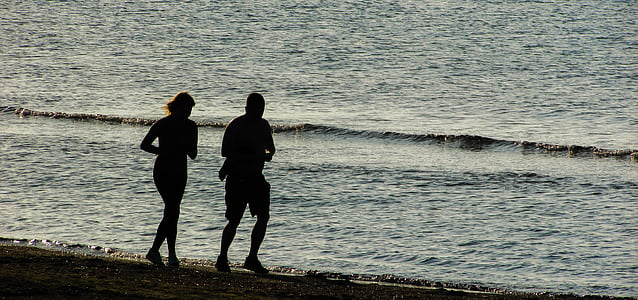 silhouette of two person running on seashore