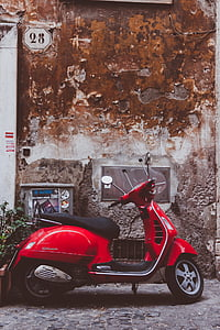 red motor scooter parked near wall