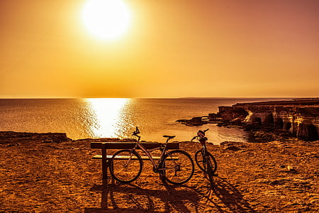 two bicycle beside bench during sunset