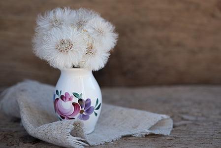 white dandelions on white floral ceramic vase