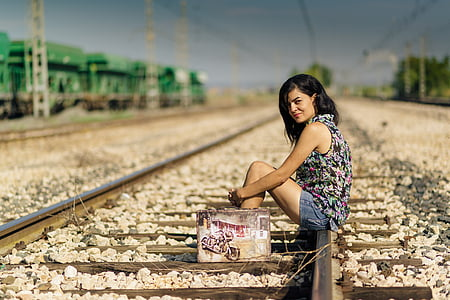 woman wearing black and multicolored sleeveless top and blue denim shorts outfit sitting on train railways under blue sky during daytime