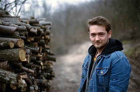 man wearing blue denim hooded jacket beside chopped tree logs during daytime
