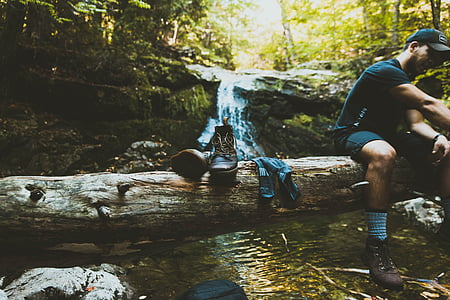 man sitting on tree trunk on top of body of water