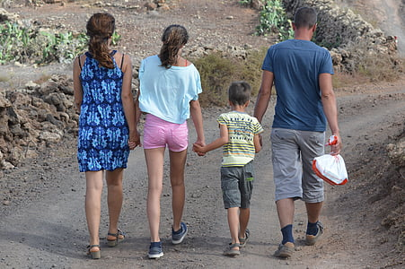 woman, girl, boy, and man holding hands together