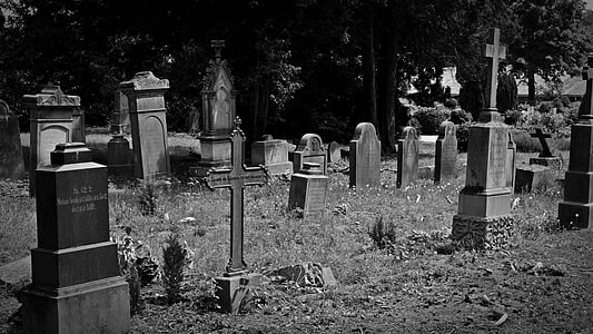grayscale photo of graveyard during daytime